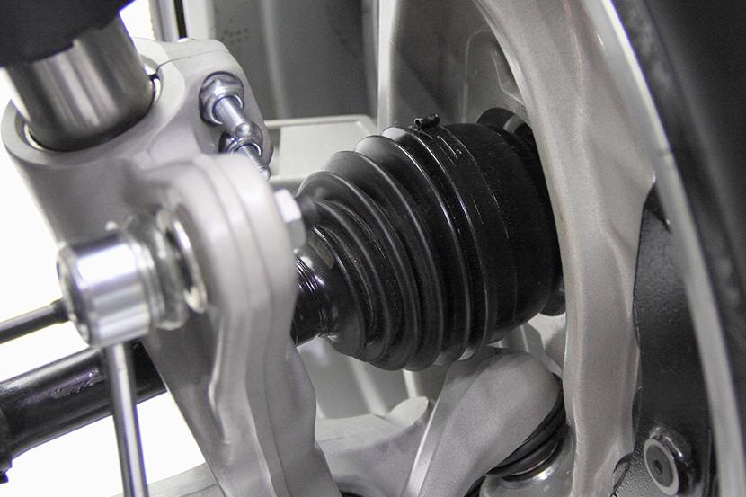 closeup of a cars driveshaft tripod cv joint shock absorber stabilizer lever disk and tire